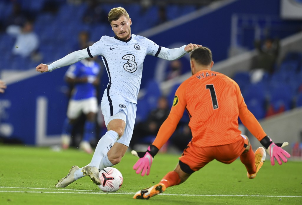 Chelsea's Timo Werner, left, is challenged by Brighton's goalkeeper Mathew Ryan during the English Premier League soccer match between Brighton and Ch...