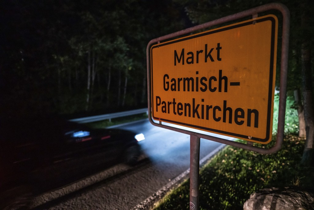FILE-In this Sept. 13, 2020 taken photo a car drives past the place name sign in Garmisch-Partenkirchen, Germany. Officials in southern Germany are co...