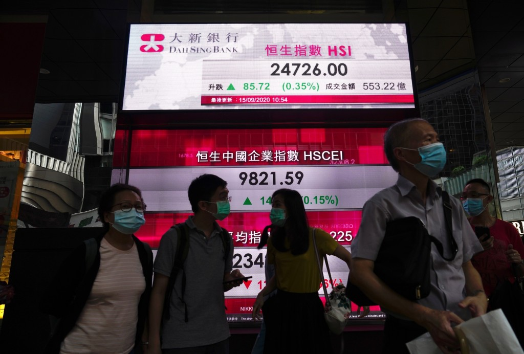 People wearing face masks walk past a bank's electronic board showing the Hong Kong share index in Hong Kong Tuesday, Sept. 15, 2020. Asian stocks wer...