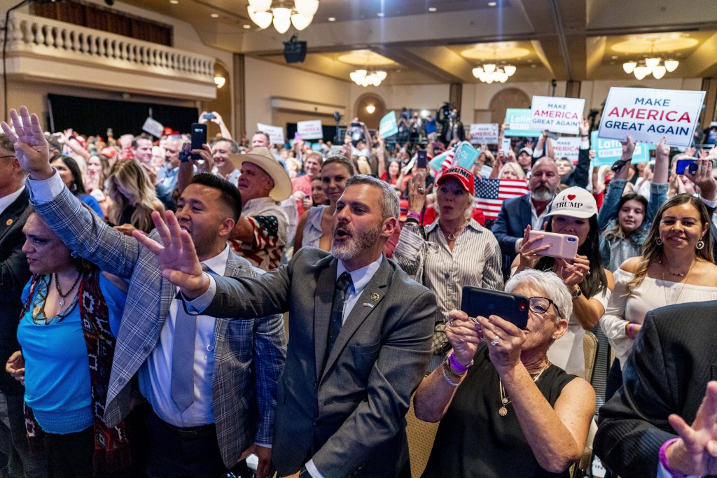 Supporters react as President Donald Trump speaks at a Latinos for Trump Coalition roundtable at Arizona Grand Resort & Spa, Monday, Sept. 14, 2020, i...