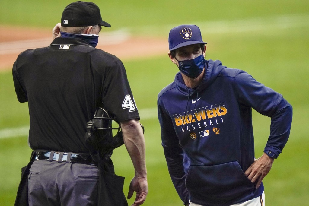 Milwaukee Brewers manager Craig Counsell talks to umpire Ron Kulpa during the first inning of the first game of a baseball doubleheader against the St...
