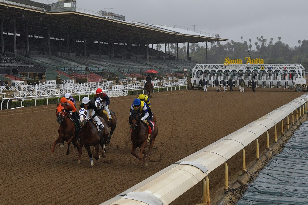 FILE - In this March 14, 2020, file photo, horses run in the fourth race at Santa Anita Park in front of empty stands in Arcadia, Calif. Opening day o...