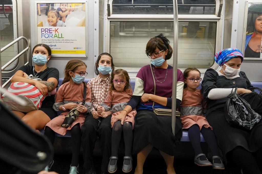 A family, some wearing face masks and some not, ride the subway, Monday, Sept. 14, 2020, in the Brooklyn borough of New York. The Metropolitan Transpo...