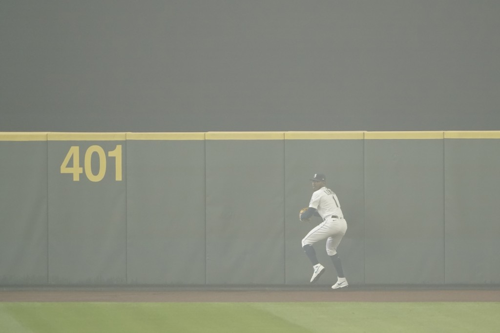 Seattle Mariners center fielder Kyle Lewis prepares to throw the ball back to the infield after making a catch as the air is filled with wildfire smok...