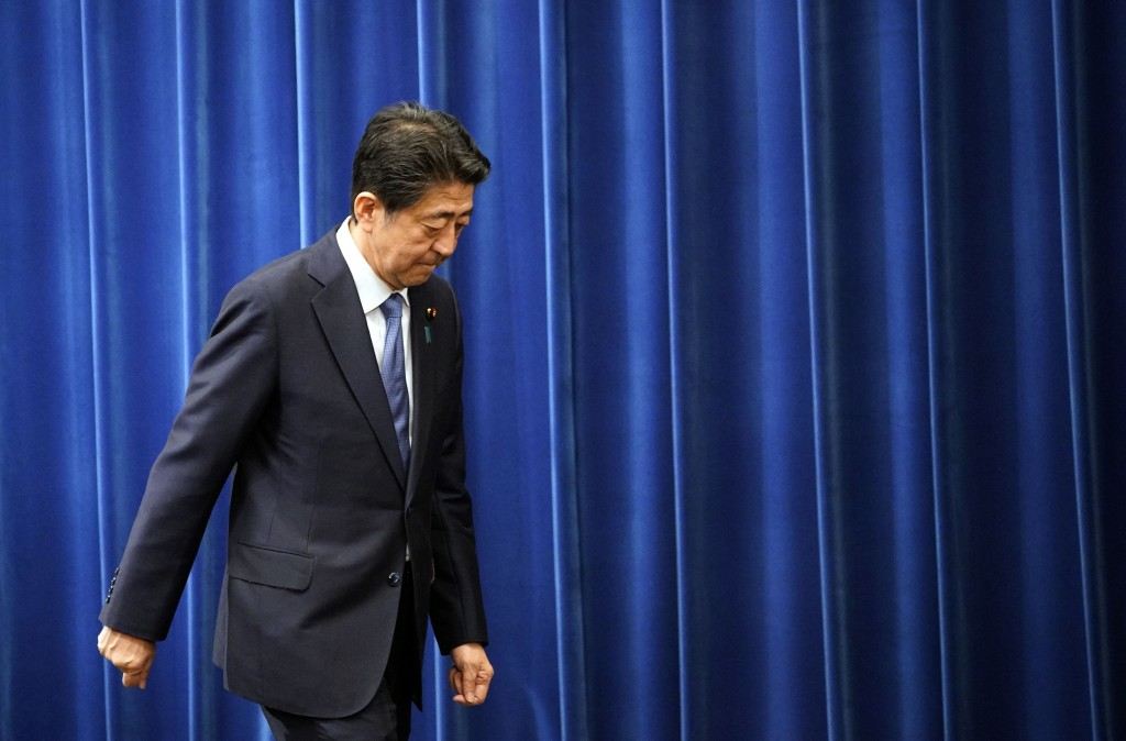 FILE - In this Aug. 28, 2020, file photo, Japanese Prime Minister Shinzo Abe walks after delivering a press conference at the prime minister official ...