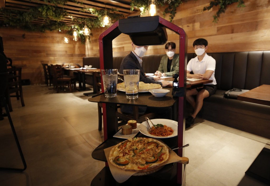 AI serving robot from KT carries foods and drinks during a demonstration at a restaurant in Seoul, South Korea, Tuesday, Sept. 15, 2020. (AP Photo/Lee...