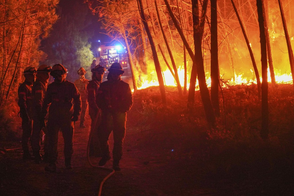 Firefighters battle a fire burning outside the village of Roqueiro, near Oleiros, Portugal, Monday, Sept. 14, 2020. Almost 1,000 firefighters are batt...