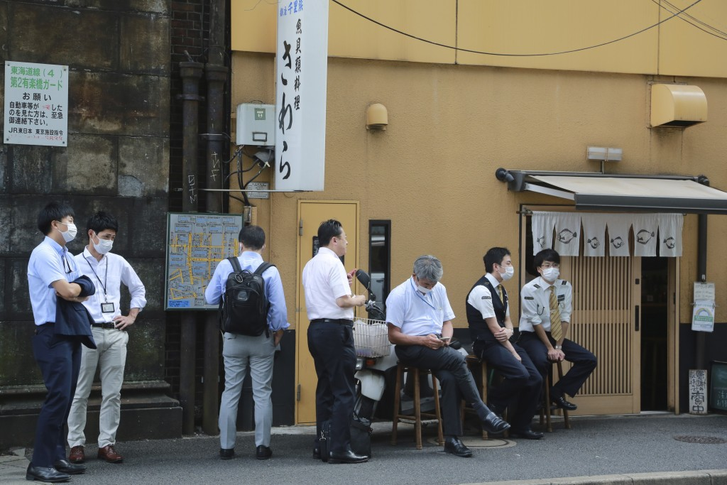 People wearing face masks to protect against the spread of the coronavirus wait to enter a Japanese restaurant for lunch in Tokyo, Tuesday, Sept. 15, ...