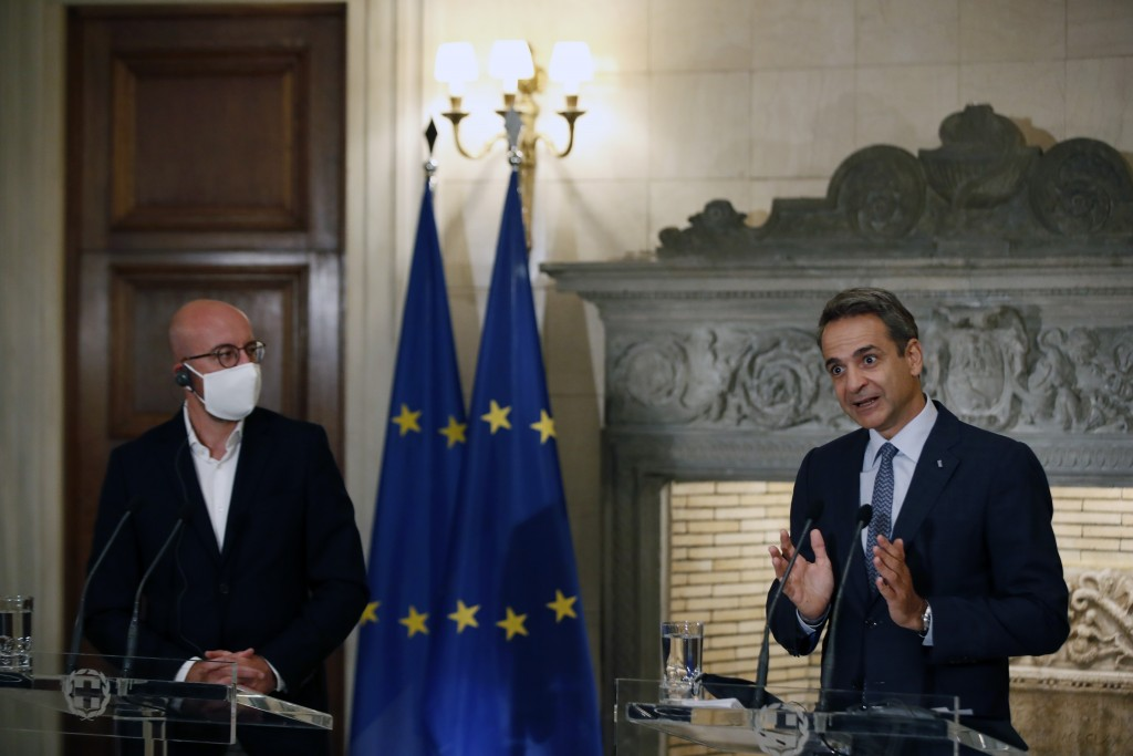 Greece's Prime Minister Kyriakos Mitsotakis, right, makes statements after his meeting with European Council President Charles Michel at Maximos Mansi...