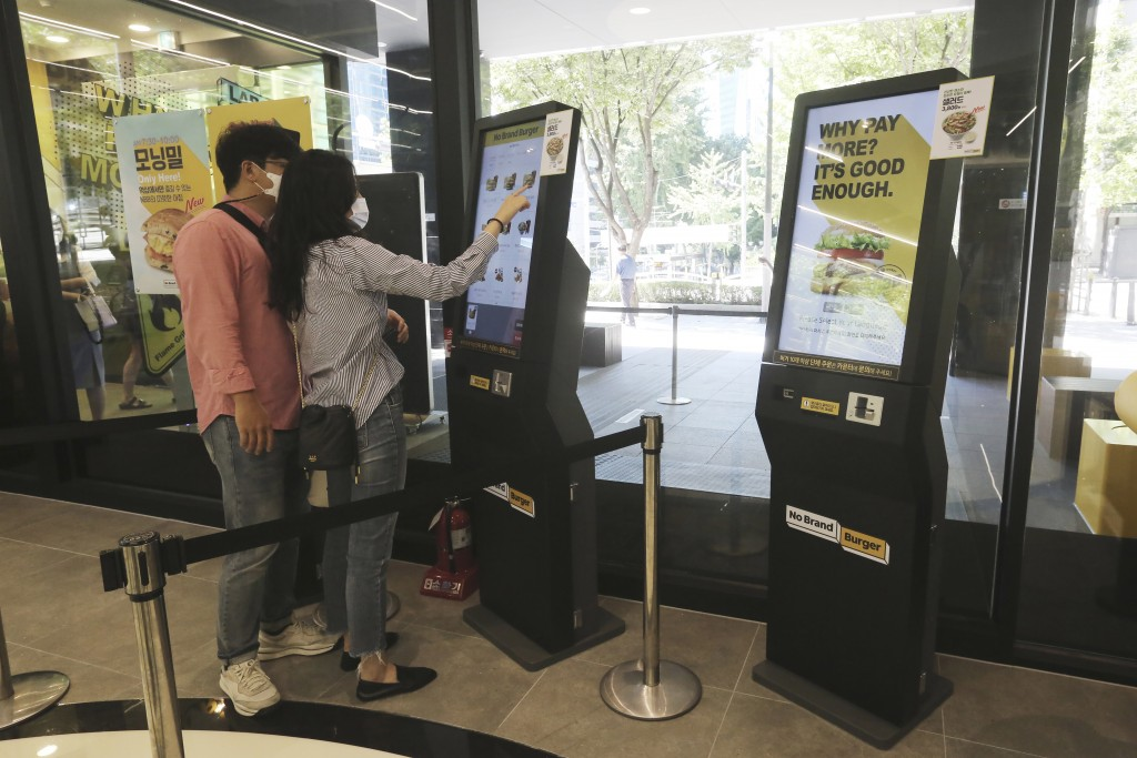 In this Sunday, Sept. 13, 2020, photo, a couple uses a touch screen kiosk to order food at No Brand Burger in Seoul, South Korea. These robotic servic...