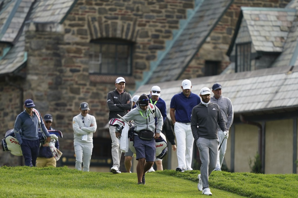 Dustin Johnson, second from right, walks down the 10th hole fairway during practice for the U.S. Open Championship golf tournament at Winged Foot Golf...