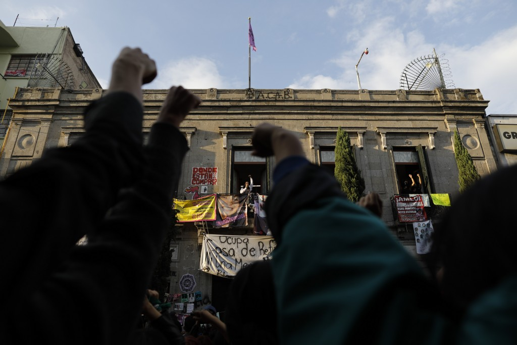 Supporters protest along with an activist as feminist and crime victims who have been occupying the offices of the governmental Human Rights Commissio...