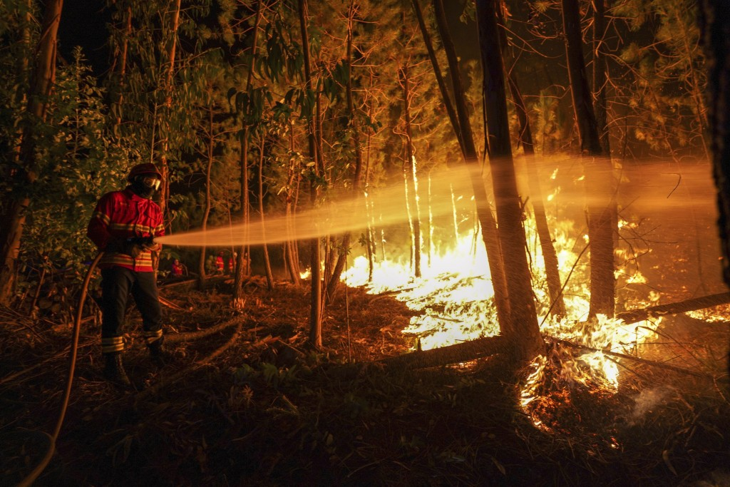 Firefighters battle a fire outside the village of Roqueiro, near Oleiros, Portugal, Monday, Sept. 14, 2020. Almost 1,000 firefighters are battling a m...