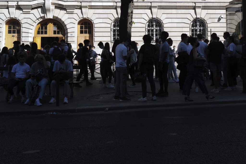 Young students, some of them wearing protective face mask as a precaution against the coronavirus, gather outside their school in Paris, Monday Sept. ...