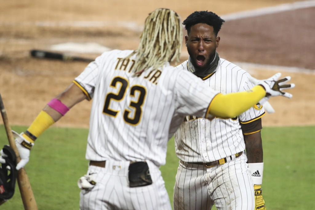 San Diego Padres' Jurickson Profar, right, reacts after scoring on a fielder's choice in the seventh inning of a baseball game against the Los Angeles...