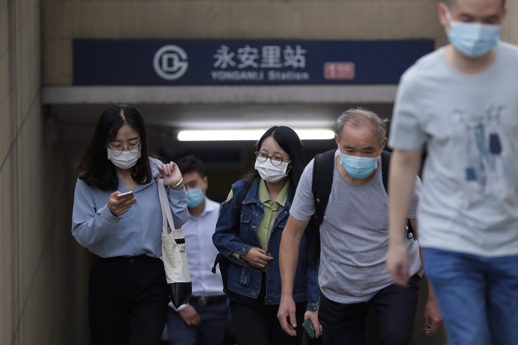 Commuters wearing face masks to help curb the spread of the coronavirus walk out from a subway station in Beijing, Tuesday, Sept. 15, 2020. Even as Ch...