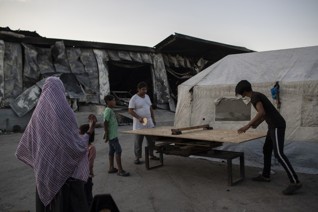 Migrants play table tennis on a makeshift table at the burned Moria refugee camp, on the northeastern island of Lesbos, Greece, Monday, Sept. 14, 2020...
