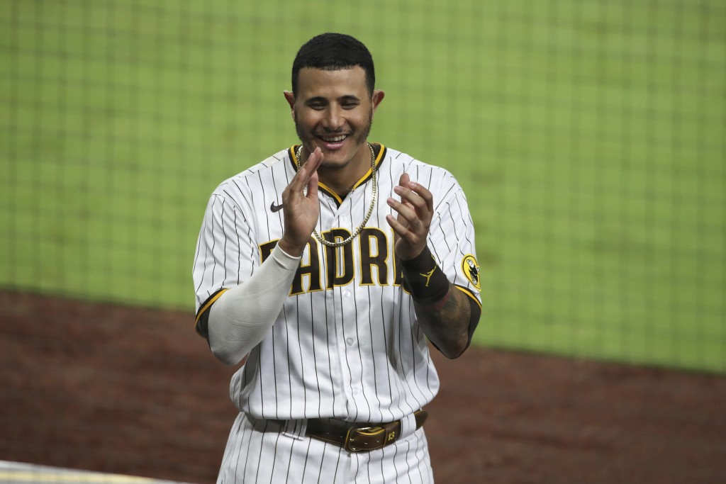 San Diego Padres' Manny Machado reacts after the Padres score against the Los Angeles Dodgers in the seventh inning of a baseball game, Monday, Sept. ...