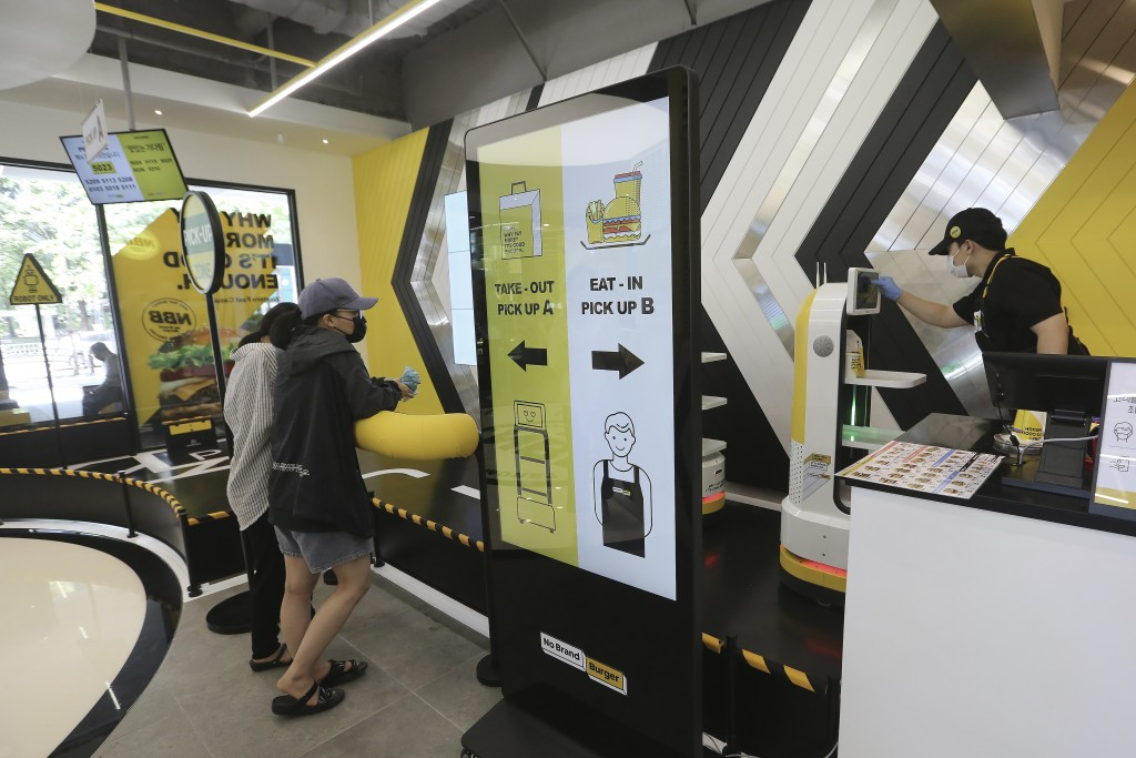 In this on Sunday, Sept. 13, 2020 photo, an employee, right, controls a robot to deliver a takeout bag with food to a customer at No Brand Burger in S...