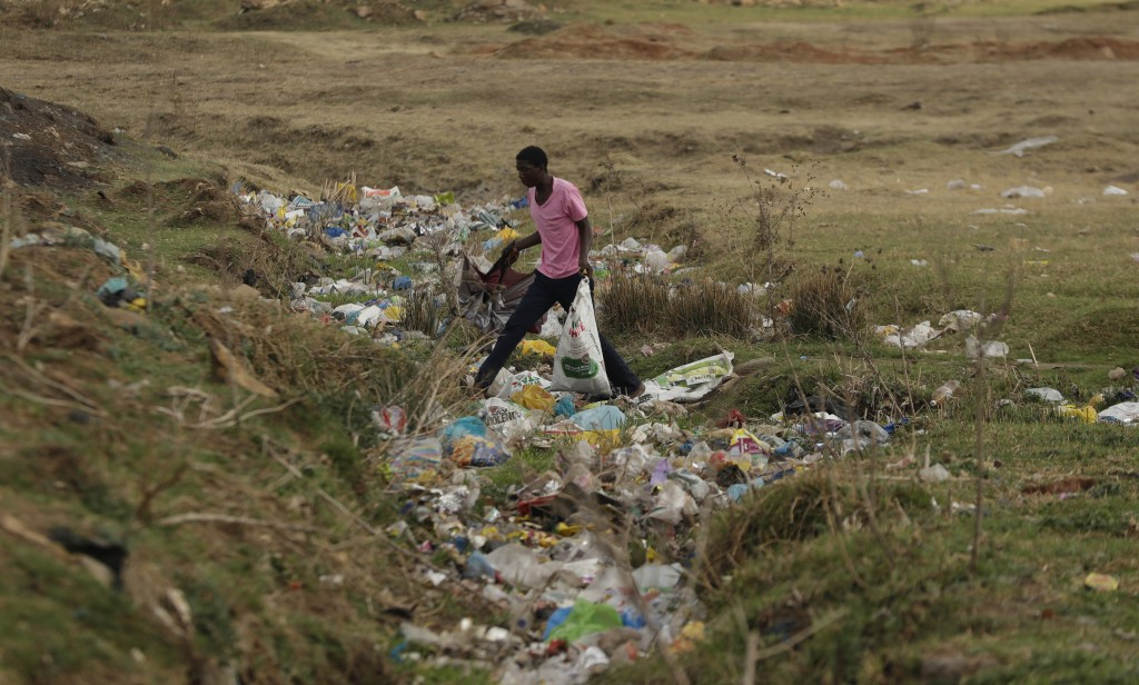 A man crosses a stream littered with plastic in the Sharpville township south of Johannesburg Monday, Sept. 14, 2020. (AP Photo/Themba Hadebe)
