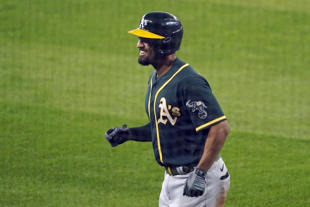 Oakland Athletics' Marcus Semien smiles as he heads to the dugout after hitting a three-run home run during the fourth inning of the first baseball ga...