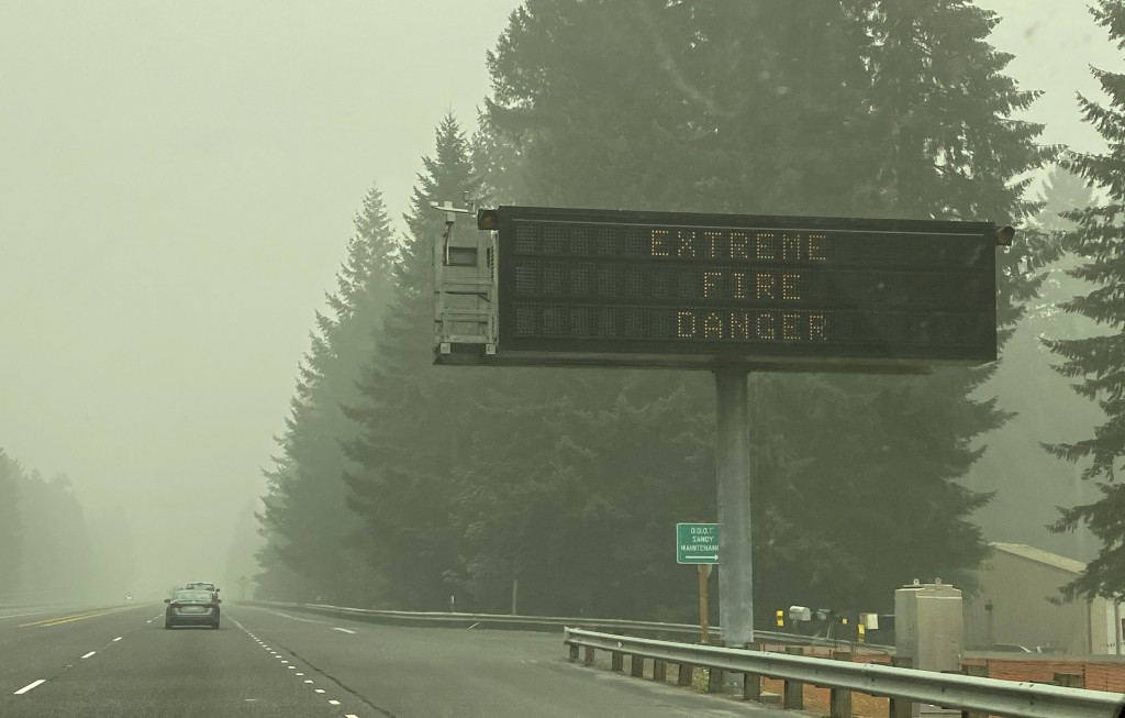 A fire warning sign is seen through the smoke in Sandy, Ore., on Monday, Sept. 14, 2020. Gov. Kate Brown said Monday she has asked President Donald Tr...