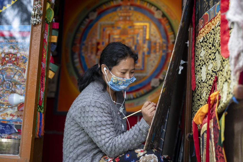 A woman wearing a mask to protect herself from the coronavirus paints a thangka, a traditional Tibetan Buddhist painting in Dharmsala, India, Tuesday,...