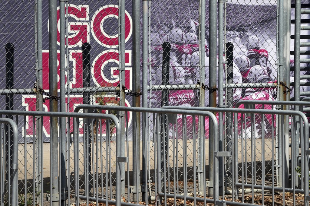 A mural showing Nebraska football players and Go Big Red lettering are seen past locked gates at Memorial Stadium in Lincoln, Neb., Tuesday, Sept. 15,...