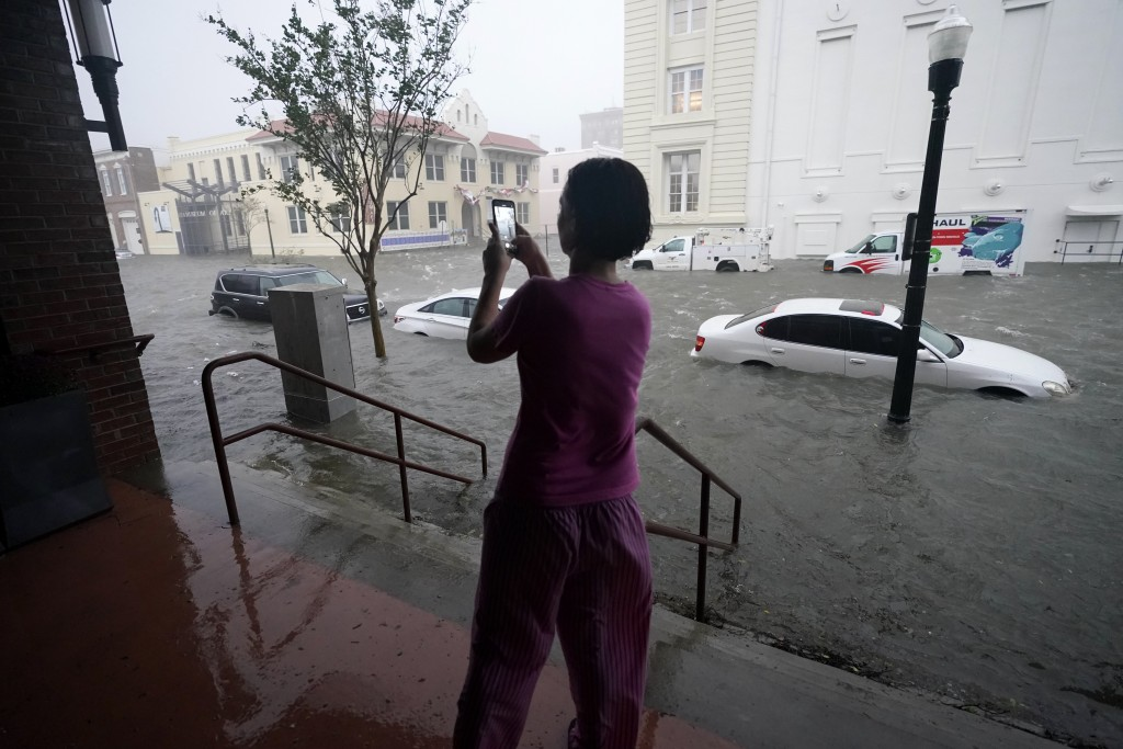 Flood waters move on the street, Wednesday, Sept. 16, 2020, in downtown Pensacola, Fla. Hurricane Sally made landfall Wednesday near Gulf Shores, Alab...