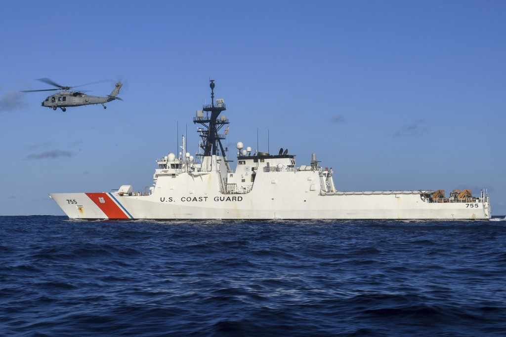 In this Aug. 25, 2020 photo provided by the U.S. Navy, an MH-60S Sea Hawk Helicopter hovers next to the Legend-class cutter USCGC Munro in the Pacific...