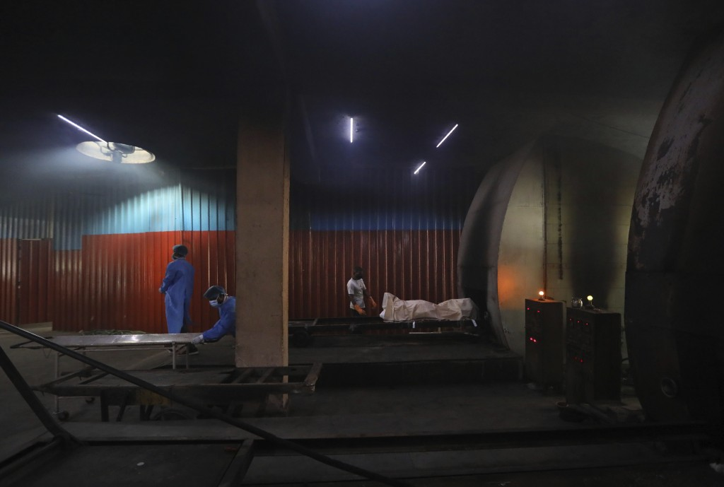 Workers remove the stretcher as other prepare to cremate the body of a COVID-19 victim in New Delhi, India, Wednesday, Sept. 16, 2020. India's total o...