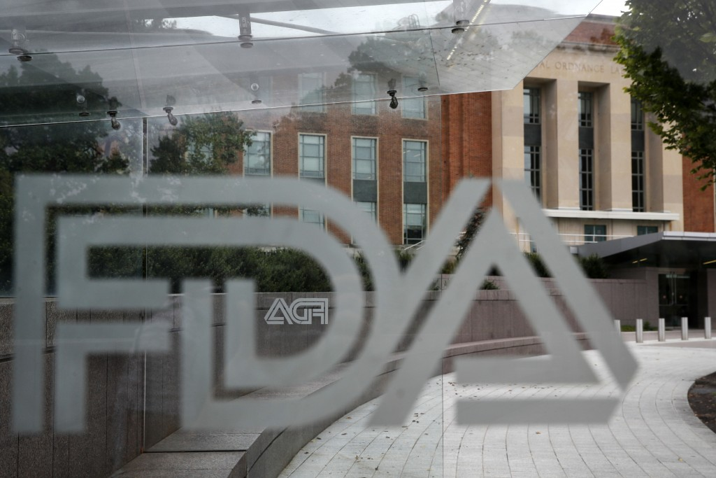 FILE - This Aug. 2, 2018, file photo shows the U.S. Food and Drug Administration building behind FDA logos at a bus stop on the agency's campus in Sil...