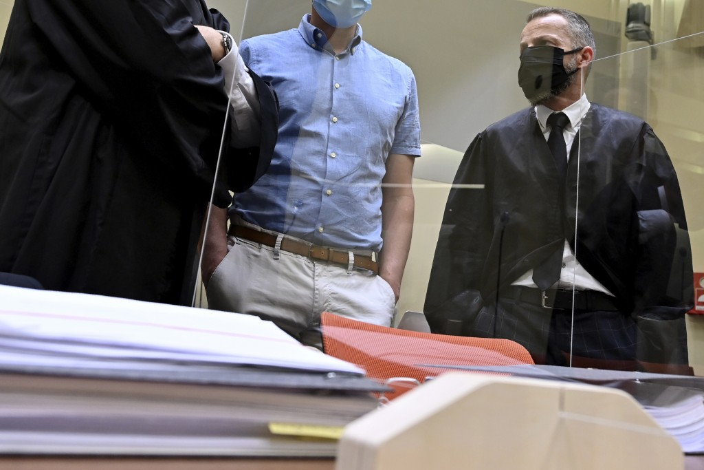At the beginning of the trial against him on suspicion of violation of the drug and doping laws, defendant Mark Schmidt, center, stands between his la...