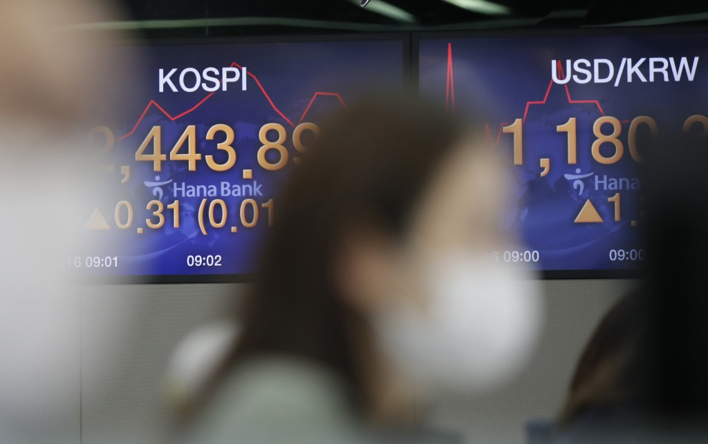A currency trader watches computer monitors near screens showing the Korea Composite Stock Price Index (KOSPI), left, and the foreign exchange rate be...
