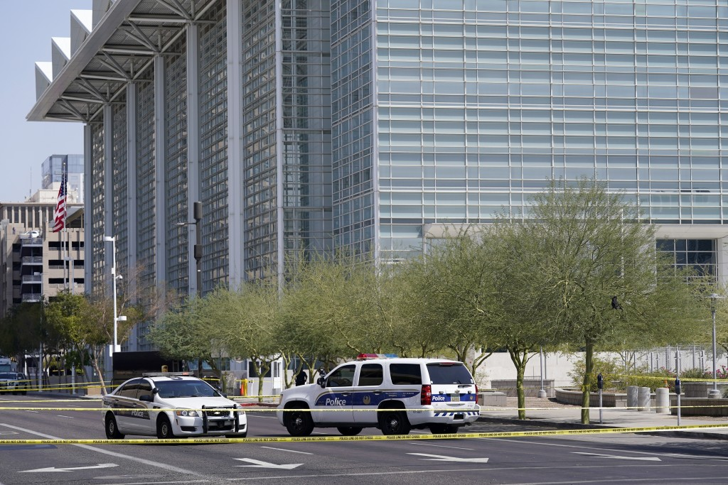 Police cars close off a street outside the Sandra Day O'Connor U.S. Courthouse in Phoenix, on Tuesday, Sept. 15, 2020. A drive-by shooting wounded a f...