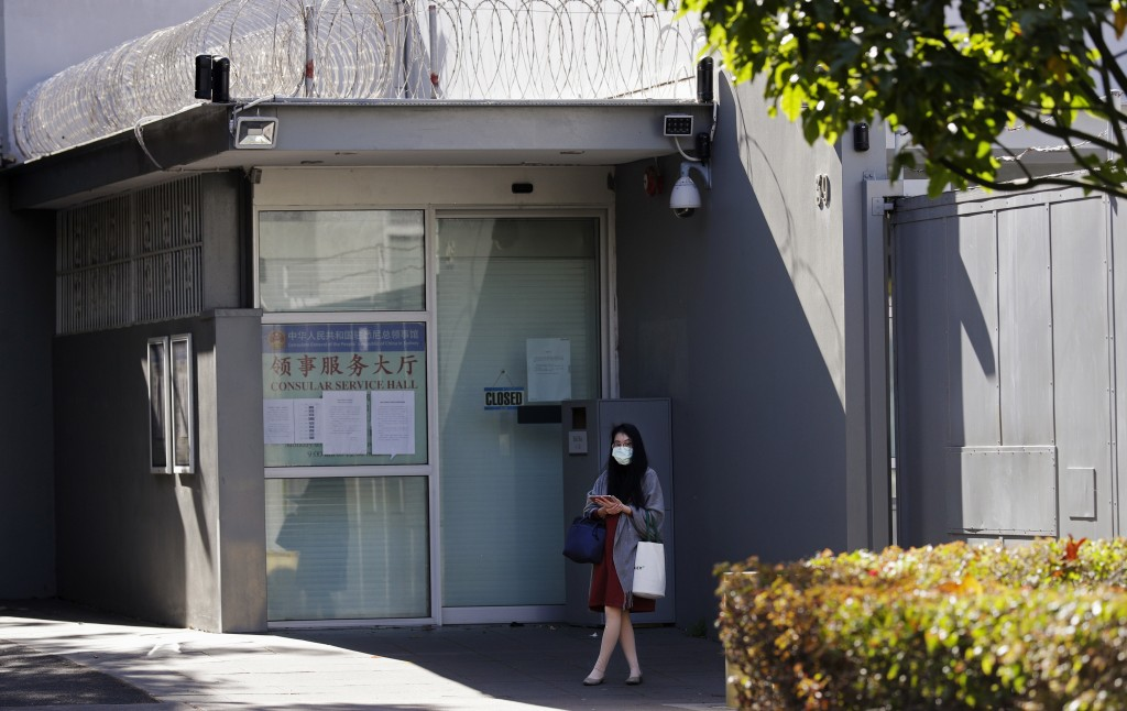 A woman stands in front of the Chinese consulate in Sydney, Wednesday, Sept. 16, 2020. A Chinese-born adviser to an Australian lawmaker has launched a...