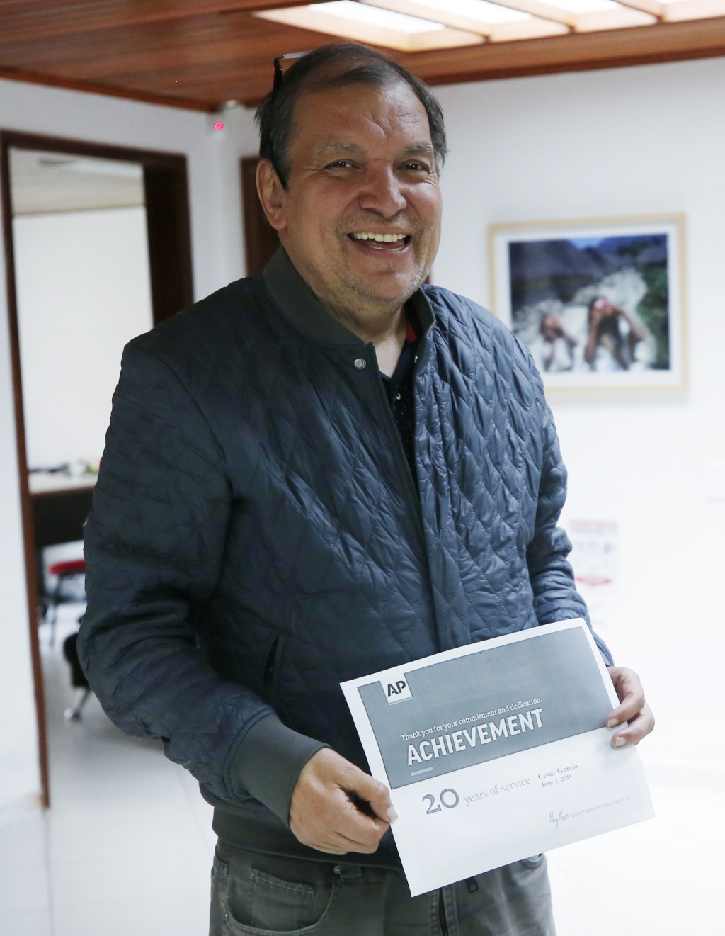 Associated Press reporter Cesar Garcia poses for a photo as he marks his 20 year anniversary with the AP at his office in Bogota, Colombia, Friday, Ma...