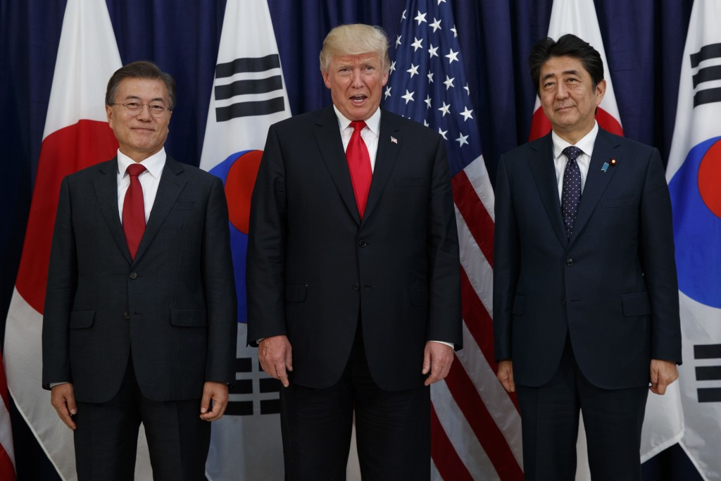 FILE- In this July 6, 2017, file photo, U.S. President Donald Trump poses with Japan's Prime Minister Shinzo Abe, right, and South Korea's President M...
