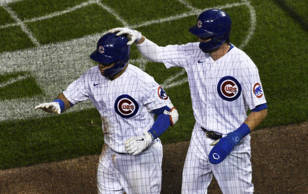 Chicago Cubs' Kris Bryant, right, pats Willson Contreras, left, on the helmet after Contreras drove in Bryant on a RBI sacrifice fly against the Cleve...