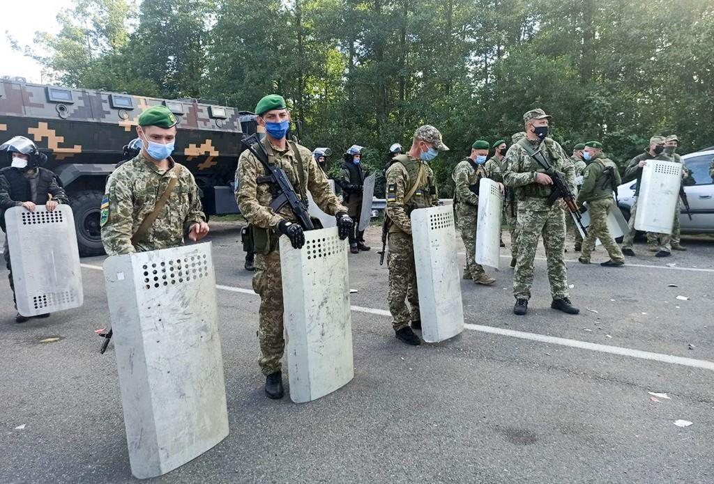 Ukrainian border guards block the road on the Belarus-Ukraine border, in Belarus, Tuesday, Sept. 15, 2020. About 700 Jewish pilgrims are stuck on Bela...