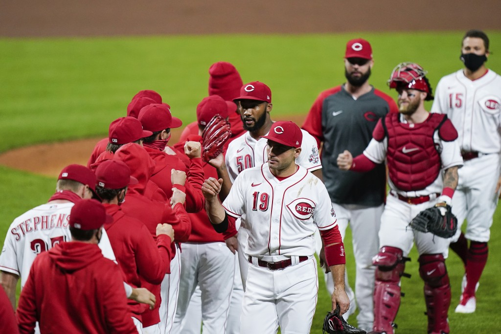 Cincinnati Reds celebrate after defeating the Pittsburgh Pirates 4-1 in a baseball game in Cincinnati, Tuesday, Sept. 15, 2020. (AP Photo/Bryan Woolst...