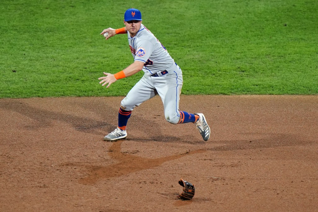 New York Mets third baseman J.D. Davis throws to first after losing his glove while fielding a single by Philadelphia Phillies' Alec Bohm during the f...