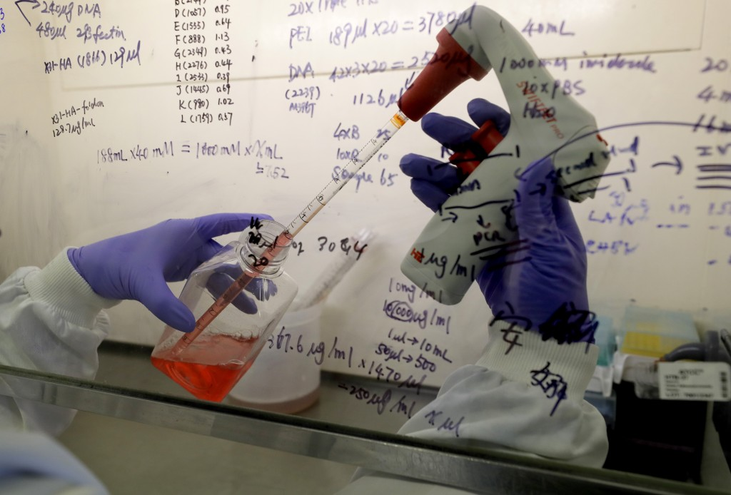 FILE - In this July 30, 2020 photo, Kai Hu, a research associate transfers medium to cells, in the laboratory at Imperial College in London. Imperial ...