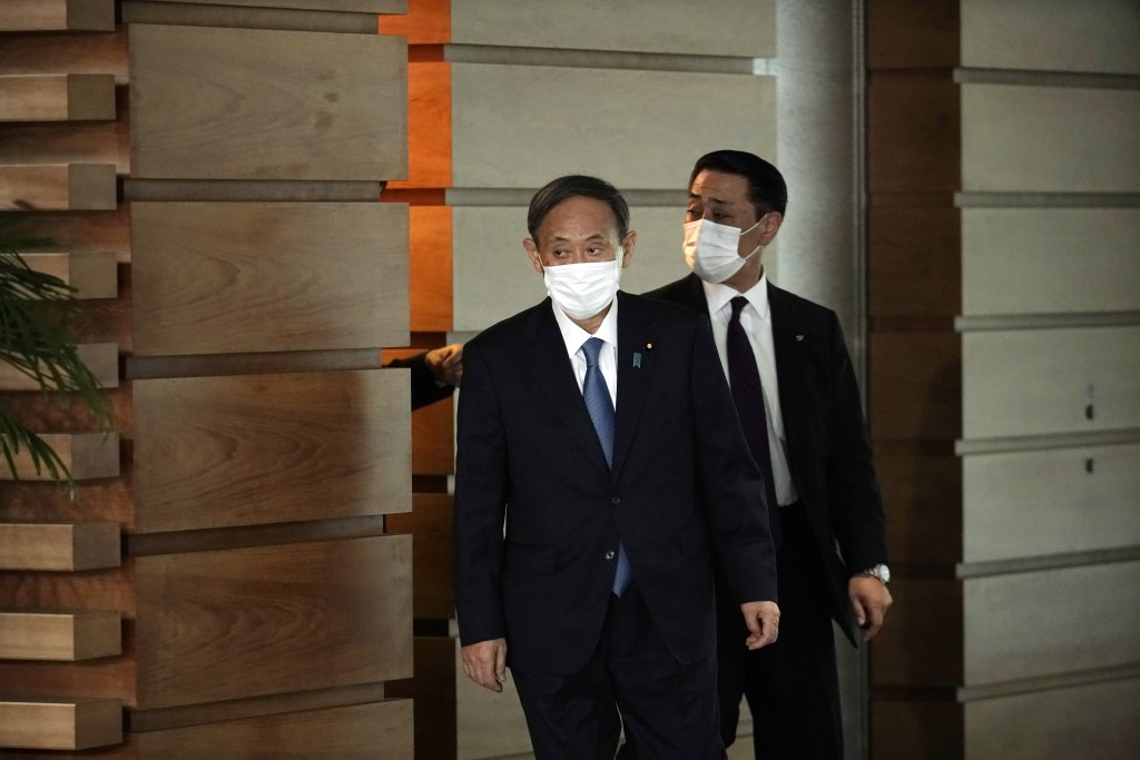 Former Chief Cabinet Secretary Yoshihide Suga, left, walks out of the prime minister's office Wednesday, Sept. 16, 2020, in Tokyo. Prime Minister Shin...