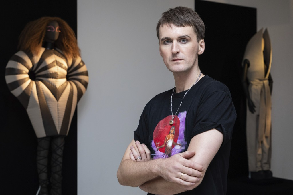 Fashion designer Gareth Pugh poses for a photograph in front of his creations, exhibited ahead of his London Fashion Week show in London, Wednesday, S...