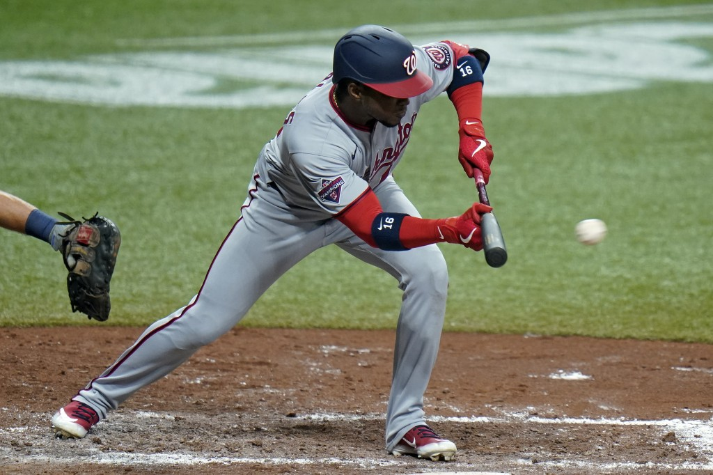 Washington Nationals' Victor Robles (16) drops down a sacrifice bunt off Tampa Bay Rays relief pitcher Ryan Yarbrough during the fifth inning of a bas...