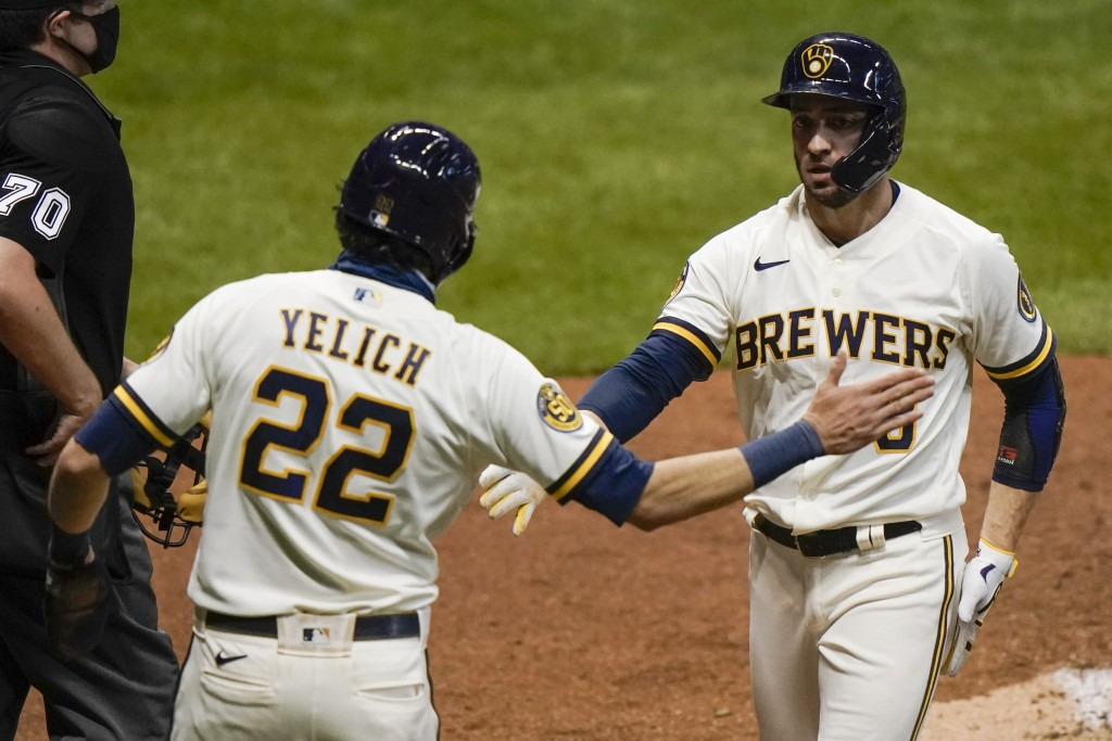 Milwaukee Brewers' Christian Yelich and Ryan Braun celebrate after scoring on a hit by Daniel Vogelbach during the third inning of a baseball game aga...