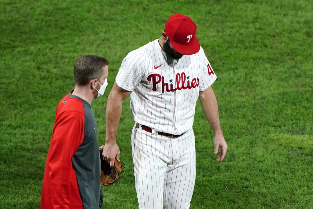 Philadelphia Phillies pitcher Jake Arrieta, right, walks to the dugout after an injury during the sixth inning of a baseball game against the New York...
