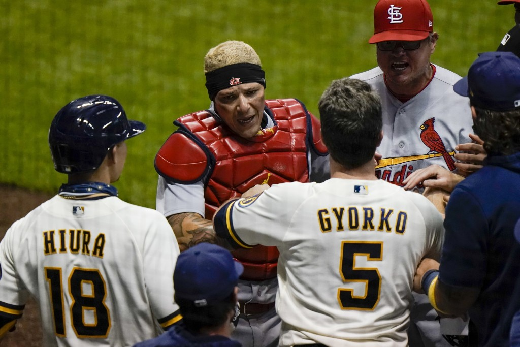 St. Louis Cardinals' Yadier Molina has words with Milwaukee Brewers' Keston Hiura and Jedd Gyorko during the fifth inning of a baseball game Tuesday, ...