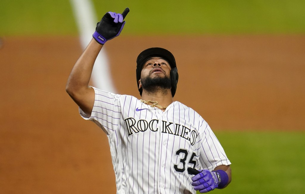 Colorado Rockies' Elias Diaz points to the sky as he crosses home plate after hitting a two-run home run against the Oakland Athletics during the fift...